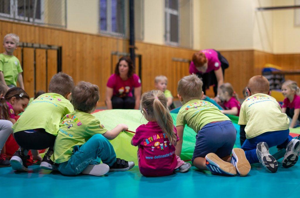 Děti cvičí sbarevným padákem. Dívky achlapci ve věku 4 - 9 let.